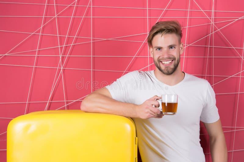 Sourire de célibataire avec la boisson de matin au réfrigérateur Tasse de prise de célibataire de thé ou de café au rétro réfrigé photographie stock