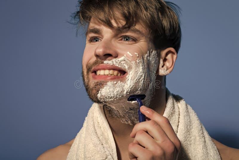 Sourire de célibataire avec la crème à raser, le rasoir et la serviette photos stock