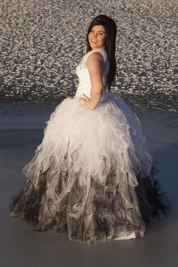 Sourire de côté de support de glace de robe formelle de femme photo stock