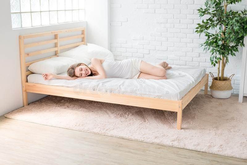 Sourire de femme heureusement sur le lit photo stock