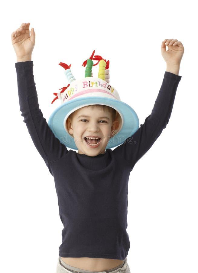 Sourire de garçon d'anniversaire heureux dans le chapeau drôle images stock