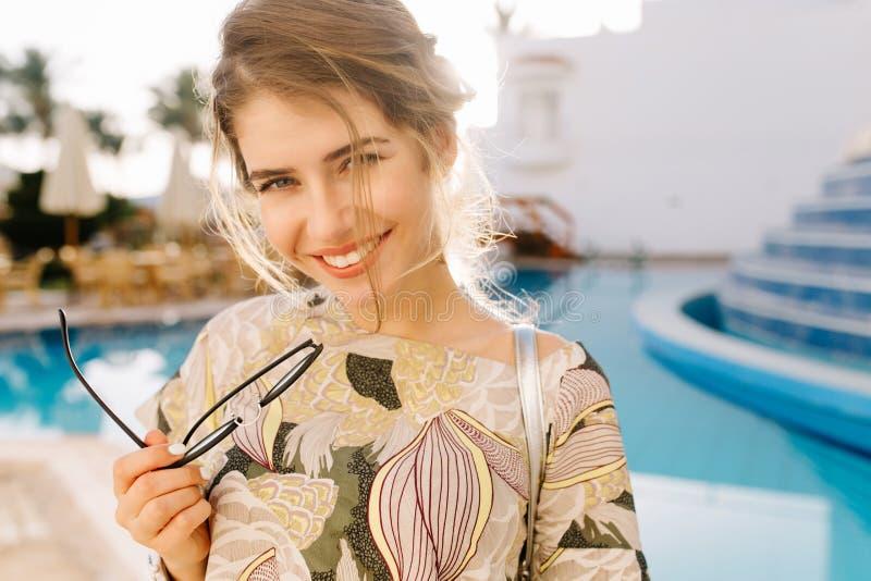 Sourire de jeune femme, tenant des verres à disposition Belle piscine, hôtel de station thermale sur le fond, station de vacances photographie stock libre de droits