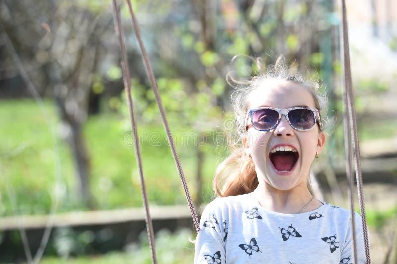 Sourire de petit enfant sur l'oscillation dans la cour d'été La fille de mode dans des lunettes de soleil ont plaisir à balancer  photos stock