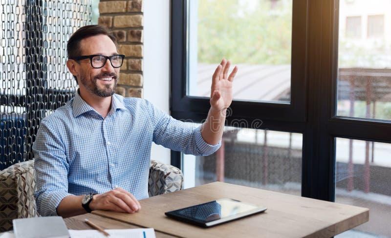 Sourire faisant des gestes le bonjour avec sa main photographie stock libre de droits