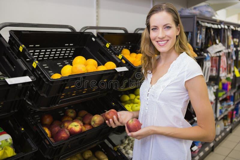 Download Sourire Femme Assez Blonde Achetant Une Pomme Photo stock - Image du détail, consommationisme: 56489340