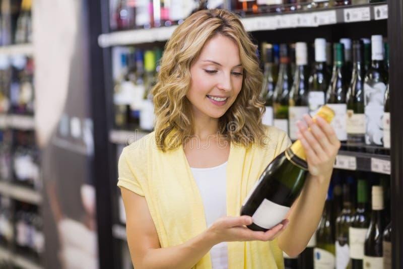 Download Sourire Femme Assez Blonde Regardant La Bouteille De Vin Photo stock - Image du marché, mémoire: 56487914