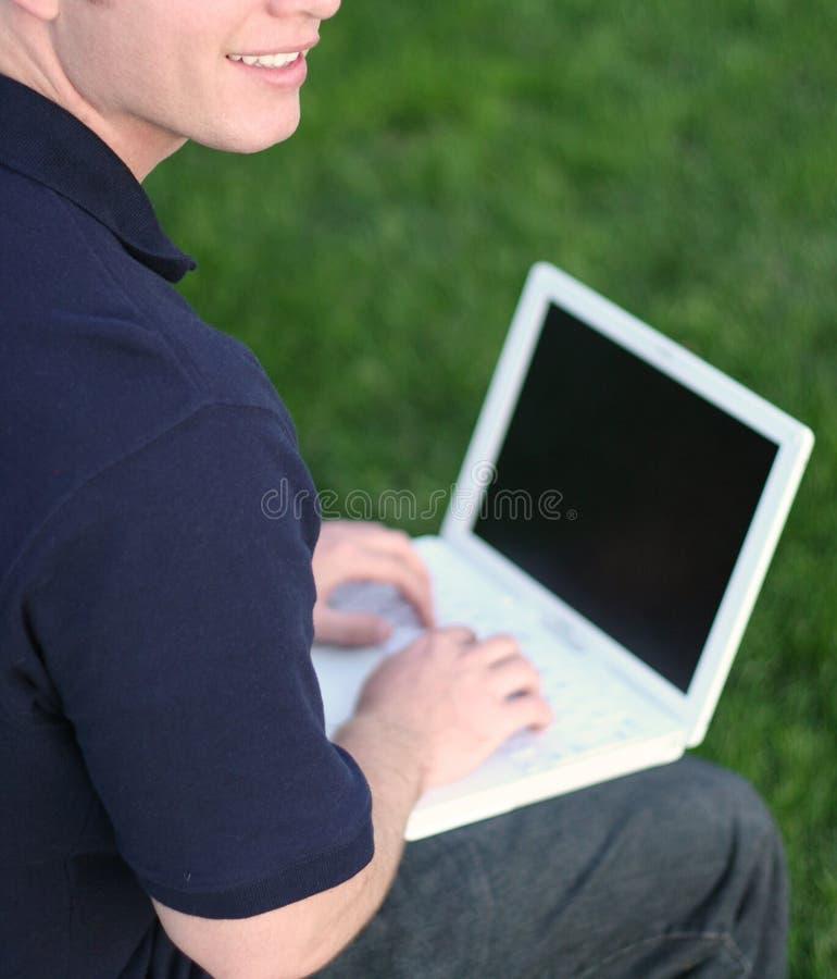 Sourire, herbe verte et ordinateur portatif photographie stock libre de droits