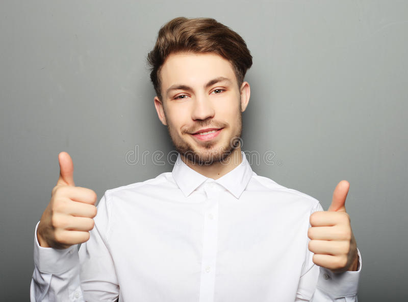 Sourire heureux d'homme bel, main de prise avec le signe correct de geste photographie stock libre de droits