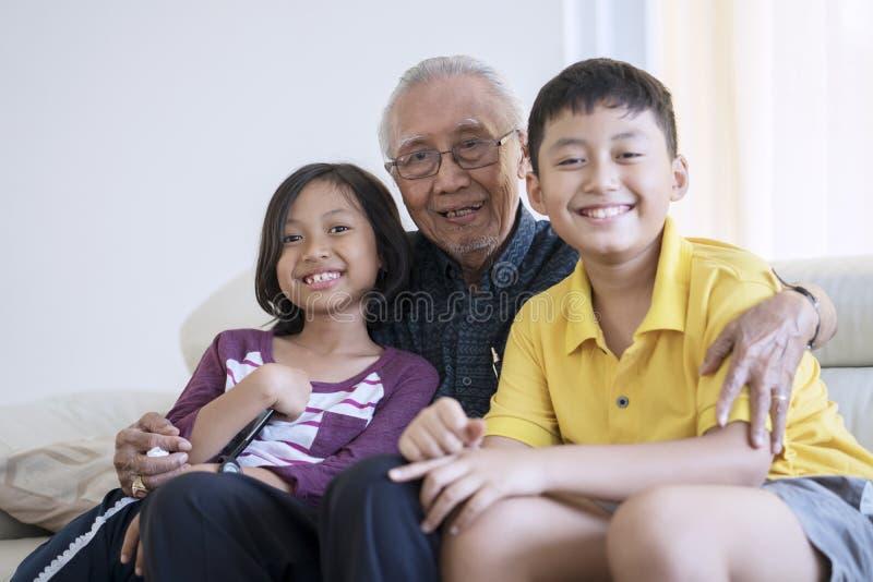 Sourire heureux d'homme supérieur et de petits-enfants images stock