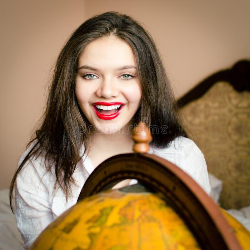 Sourire heureux de belle de jeune femme étudiante attirante élégante de brune avec le rouge à lèvres rouge au globe regardant l'a photographie stock libre de droits