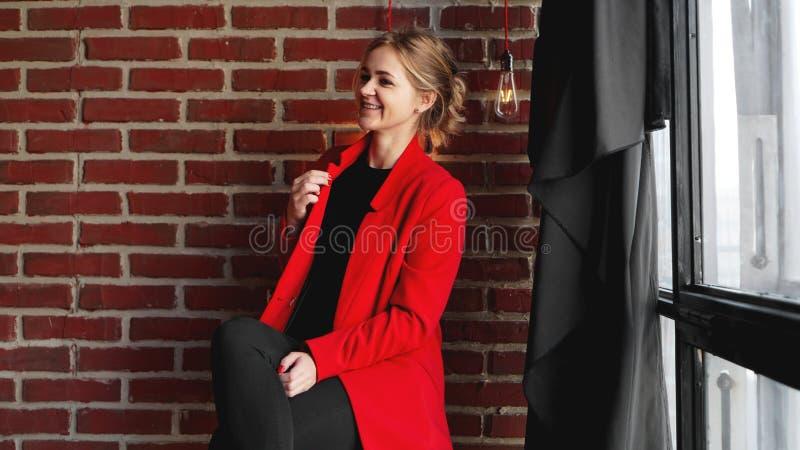 Sourire heureux de femme d'affaires utiliser la veste rouge au-dessus du mur de briques de bureau photos libres de droits