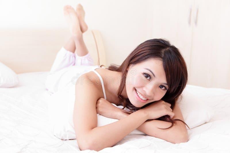 Sourire heureux de femme tout en se trouvant sur le lit photos libres de droits