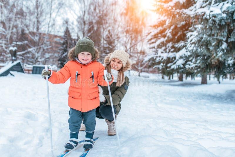 Sourire heureux de jeune femme de mère, garçon de fils rires de 3 années En hiver, en dehors de parc, le fond est des dérives de  photos libres de droits