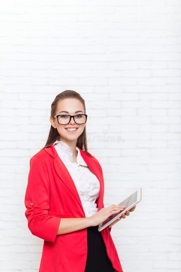 Sourire heureux en verre rouges de veste d'usage d'écran tactile de tablette d'utilisation de femme d'affaires image stock