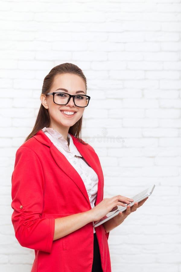 Sourire heureux en verre rouges de veste d'usage d'écran tactile de tablette d'utilisation de femme d'affaires photo libre de droits