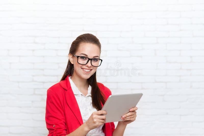 Sourire heureux en verre rouges de veste d'usage de tablette d'utilisation de femme d'affaires photos libres de droits