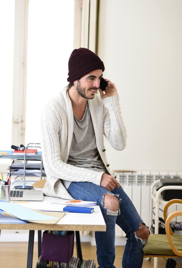 Sourire informel de regard de hippie à la mode d'homme d'affaires heureux au téléphone portable image stock
