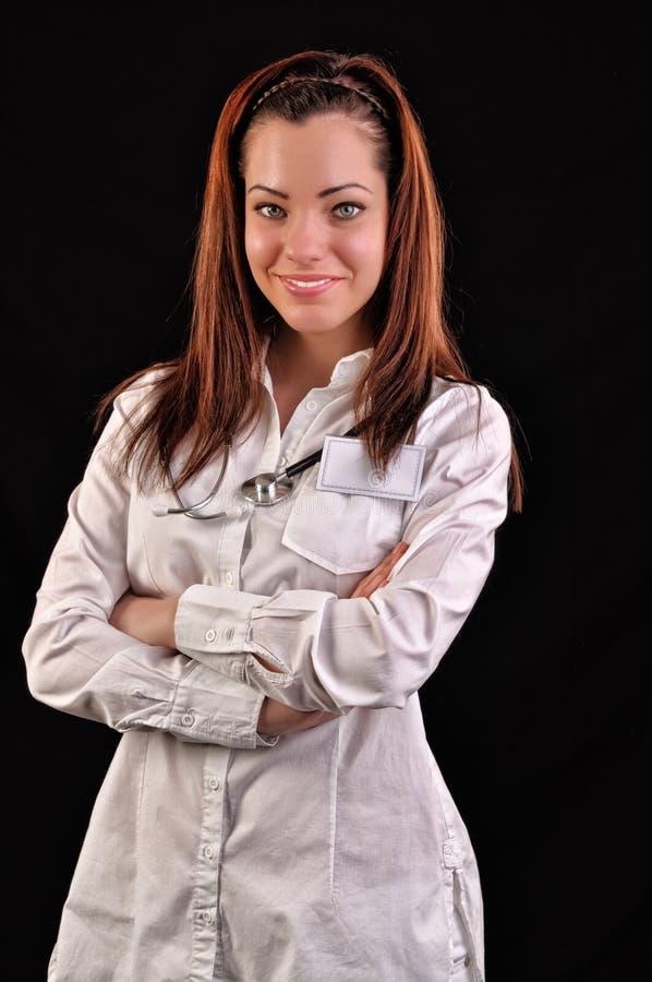 Sourire médical attrayant de docteur de femme D'isolement au-dessus du CCB noir photo stock