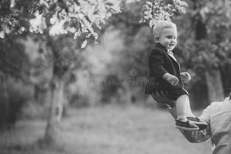 Sourire mignon d'enfant en bas âge dans le costume, chemises, espadrilles sous l'arbre, mode image stock