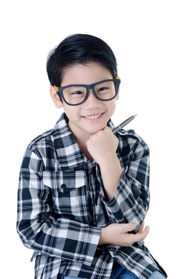 Sourire mignon de petit garçon avec l'isolat en verre d'oeil sur le backgrou blanc photographie stock libre de droits