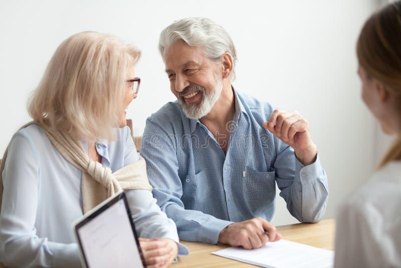 Sourire parlant de famille supérieure heureuse lors de la réunion avec l'annonce financière photographie stock