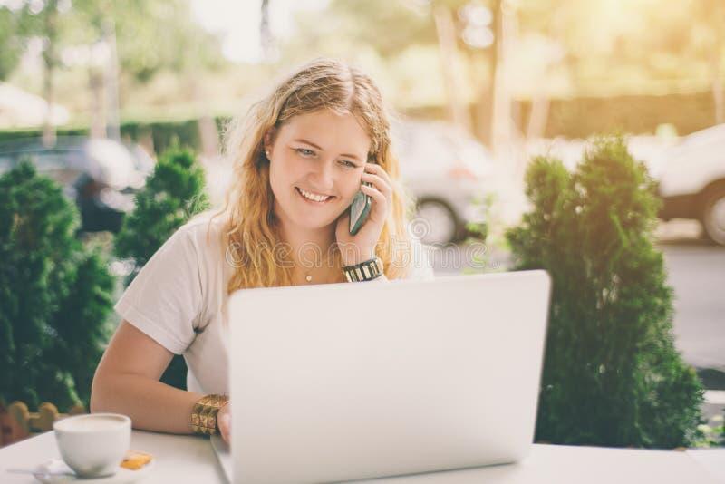 Sourire plus la fille de modèle de taille avec l'ordinateur portable et le smartphone photo stock