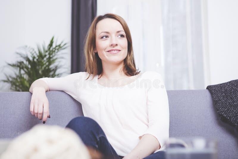 Sourire se reposant de fille d'une chevelure brune heureuse sur un sofa photographie stock