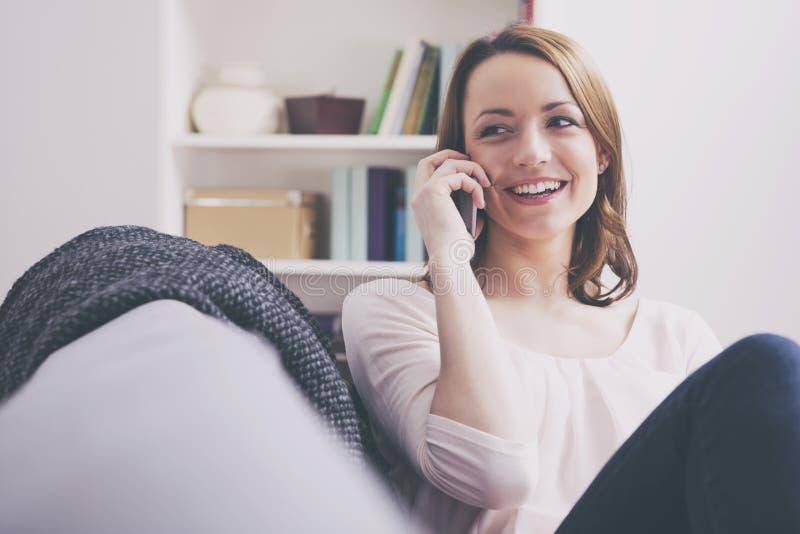 Sourire se reposant de fille d'une chevelure brune heureuse sur un sofa photographie stock libre de droits