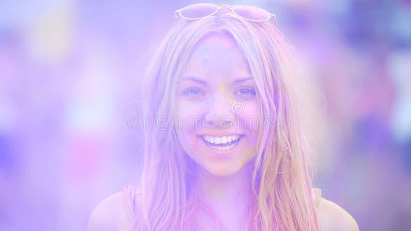 Sourire sincère de la jeune femme gaie ayant l'amusement au festival passionnant de couleur photos libres de droits
