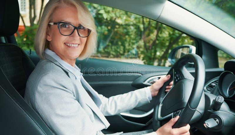 Sourire toothy âgé de femme tout en conduisant une voiture photos stock