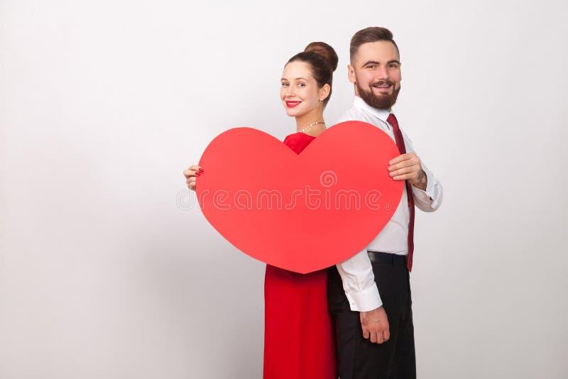 Sourire toothy de couples de bonheur, tenant le coeur, se tenant de nouveau à b photographie stock