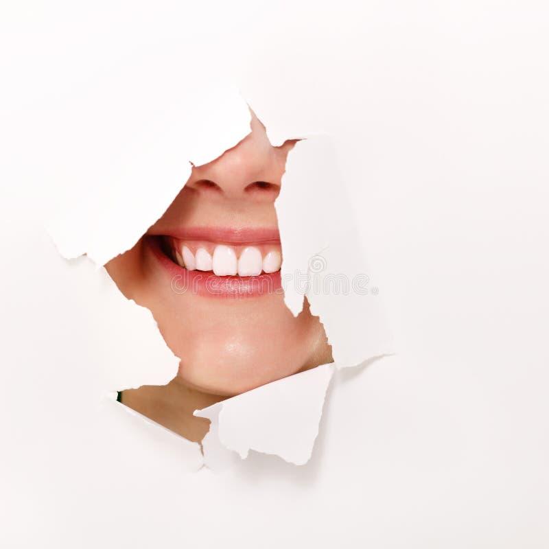 Sourire Toothy de fille de l'adolescence gaie par le trou du blanc photographie stock libre de droits