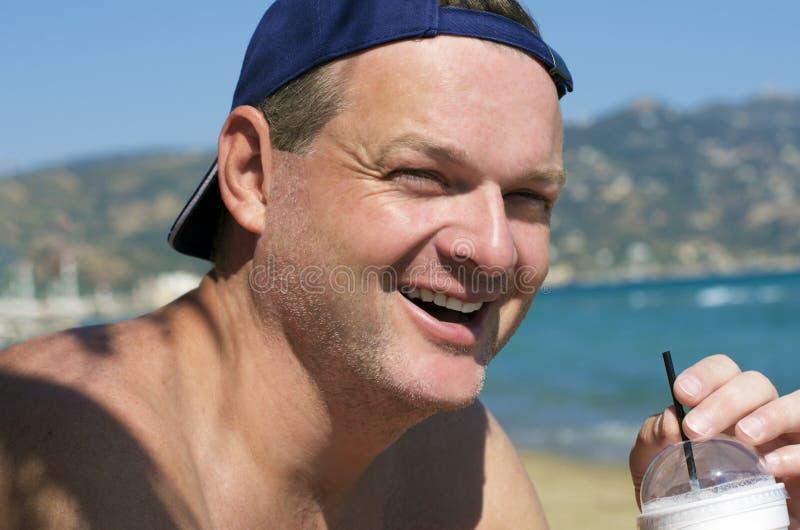 Sourires d'homme avec le cocktail dans des mains largement photographie stock