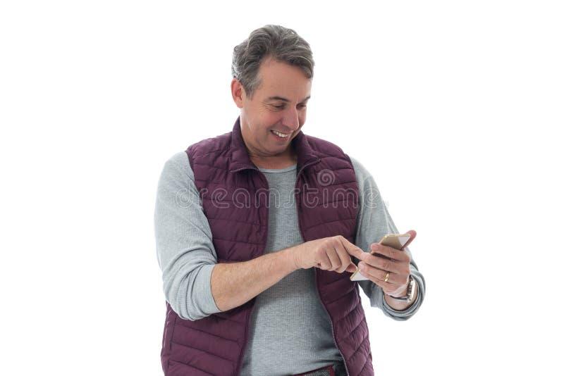 Sourires d'une cinquantaine d'années et types d'homme sur le téléphone portable Il porte un r images stock