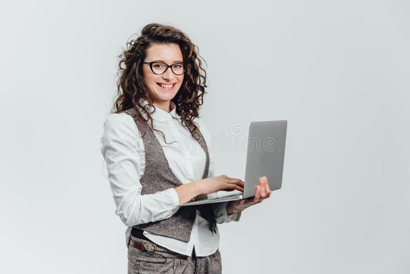 Sourires de jeune fille de BBeautiful Travaux sur un ordinateur portable dans les verres et une chemise blanche image libre de droits
