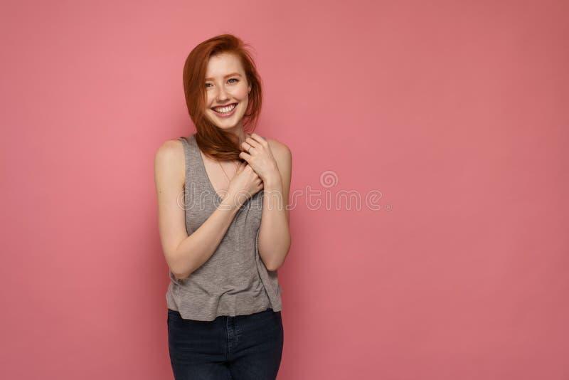 Sourires roux de fille à la caméra croisant ses mains sur son coffre photo stock