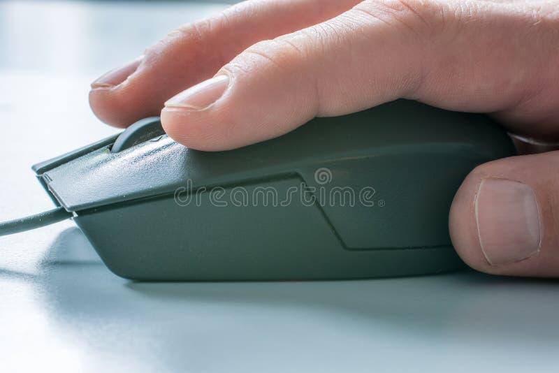 Souris d'ordinateur avec la main de l'homme à un bureau blanc à l'arrière-plan photo stock