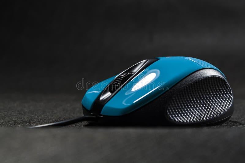 Souris d'ordinateur de couleur bleue lumineuse Détails noirs plastique Technologies modernes Fond noir Ordinateur photos stock