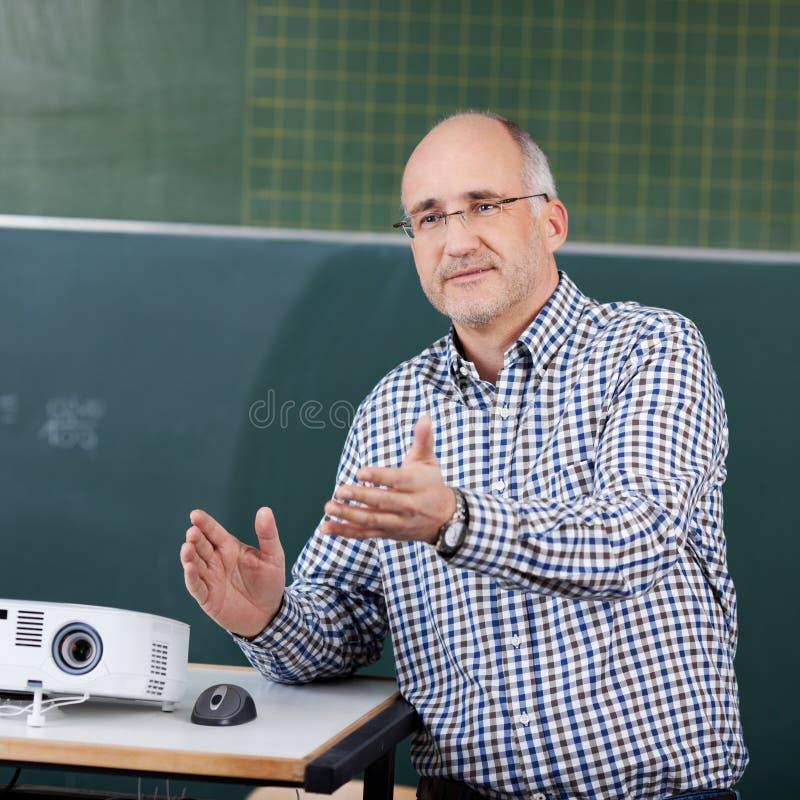 Souris de professeur With Projector And faisant des gestes dans la salle de classe photo libre de droits