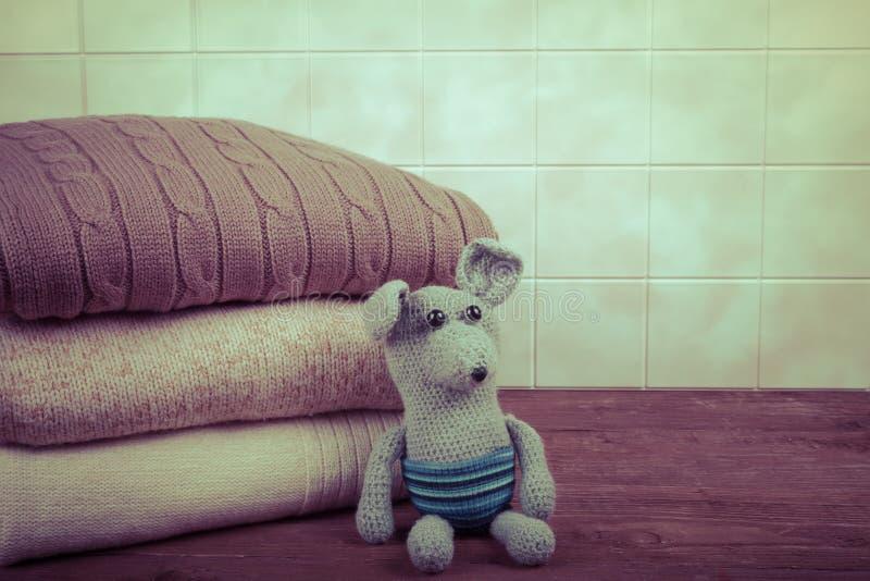 Souris ou rat tricotée de jouet avec la pile de vêtements tricotés sur l'OE photographie stock libre de droits