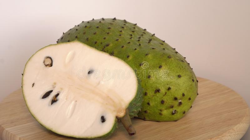 Soursop, Annona muricata L with slice on wooden cutting board stock image