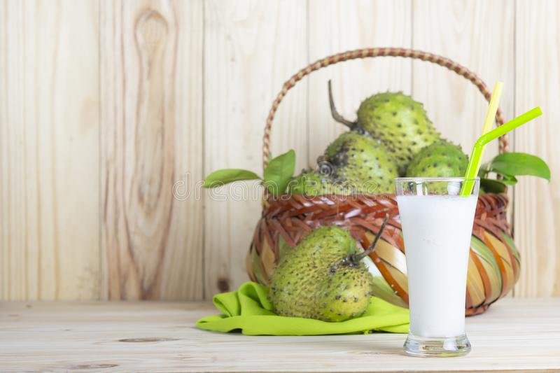 Soursop juice with soursop fruit in basket on wooden table. stock photography