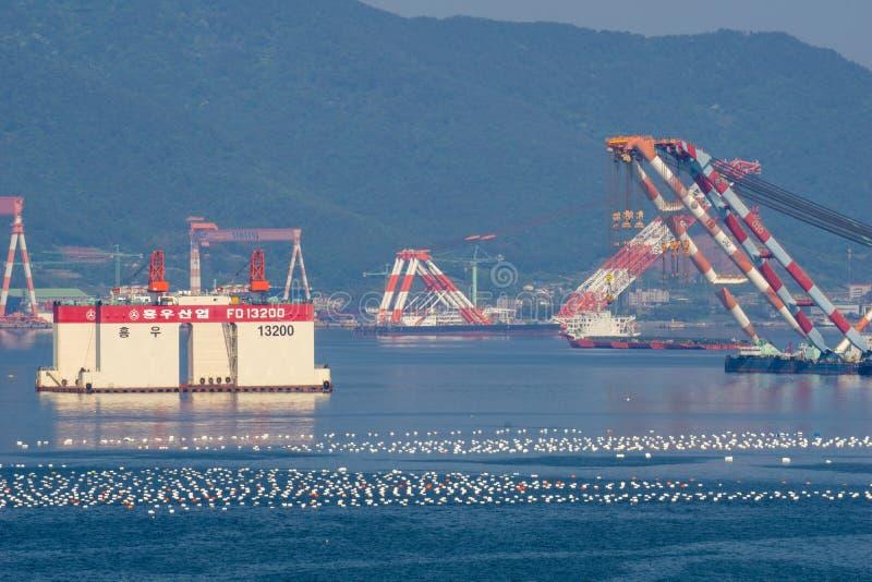 Sous construit outre des ancres de plate-forme de rivage dans la baie devant des industries lourdes de Samsung ou de SHI en île d photographie stock