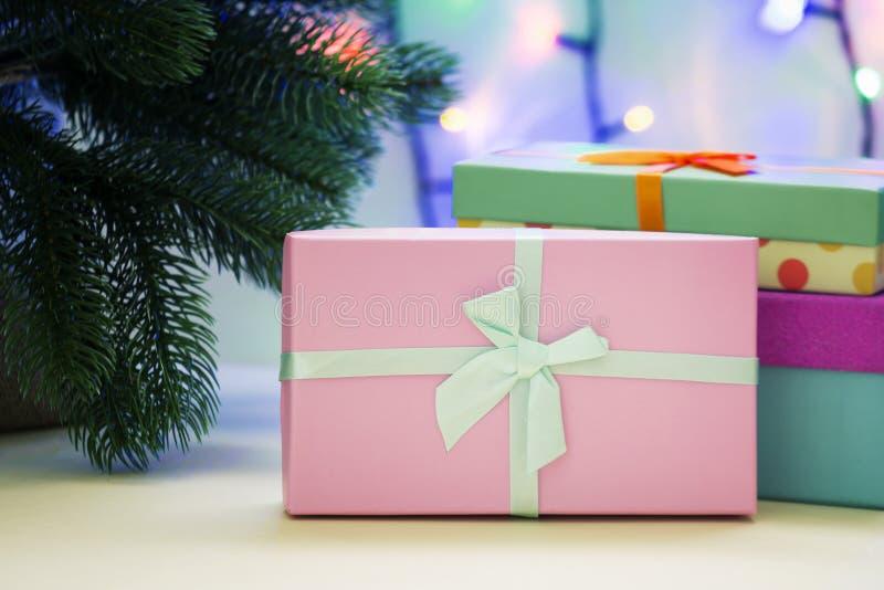 Sous l'arbre de nouvelle année sont les cadeaux Dans le premier plan, une boîte rose décorée d'un ruban bleu cintre image stock