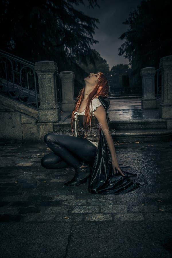 Sous la tempête, belle femme de vampire dans la porte de palais, pluie photos libres de droits