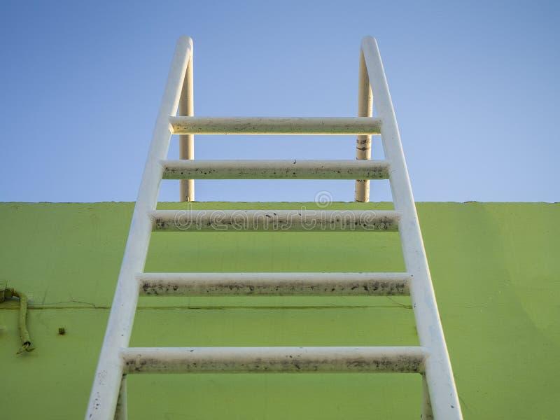 Sous la vue de l'échelle en acier sur le fond vert et le ciel bleu image libre de droits