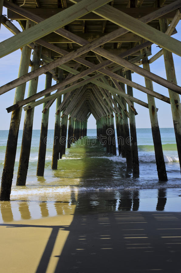 Sous le pilier de plage de coucher du soleil image stock