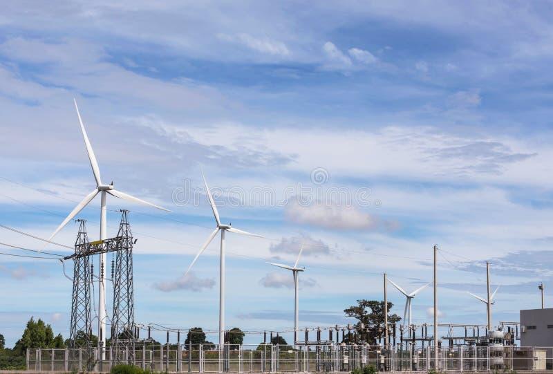 Sous-station à haute tension de pylône de courant électrique avec de l'énergie éolienne renouvelable de turbines de vent photos stock
