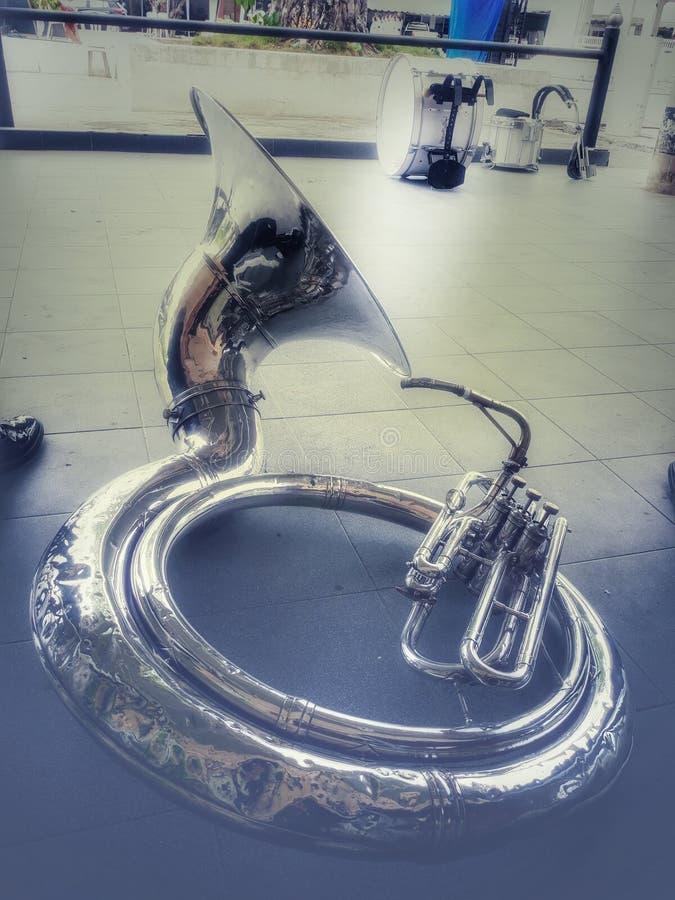 Sousaphonen är mässingsinstrument som används i mässingsmusikband Ställe på en bakgrund för tappningsignalfärg royaltyfri bild