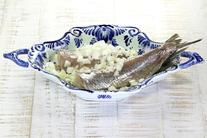 Soused herring. In delftware bowl on wooden background royalty free stock image